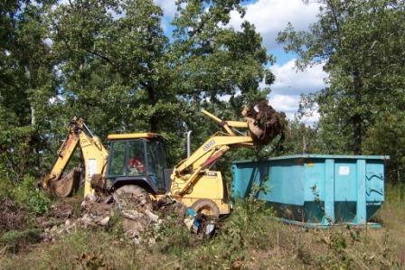 Backhoe loads trash into dumpster at Gooch Sink