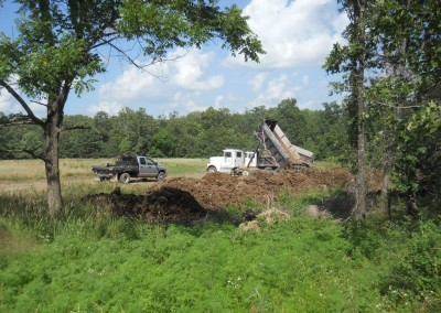 Dump trucks empty fill in ravine in pasture 6-21-14