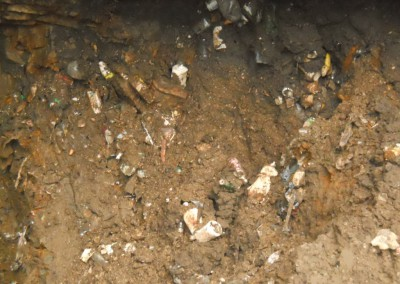 steep walls of trash and sediment next to cave entrance